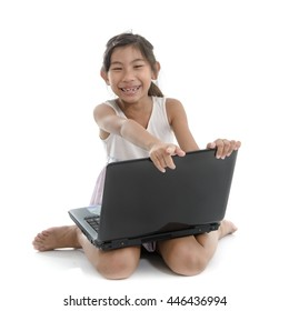Happy Asian child playing lapton on white floor.