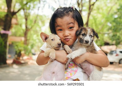 Happy Asian child playing with Thai dog. Homeless poor kid holding cute pet at home.