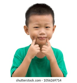 Happy Asian child pointing his cheeks and smiling. Portrait of young boy showing body parts isolated on white background.