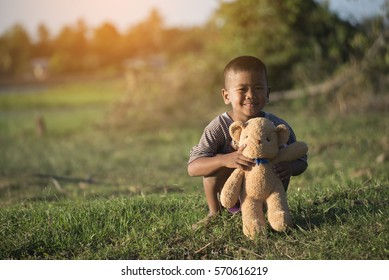 Happy Asian Child (poor kid) smiling and hugging teddy bear, sitting on grass. Teddy Bear and child are best friends. Friendship and homeless people concept.