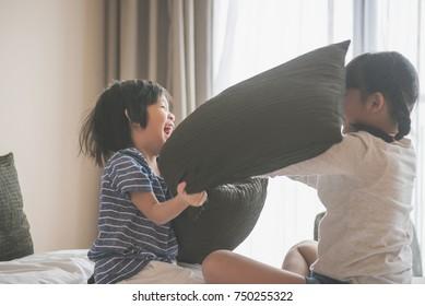 Happy Asian child ren having Pillow Fight in Hotel Room