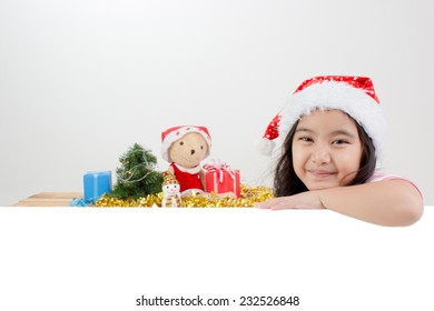 Happy Asian child in Santa hat with Christmas decorations and white board