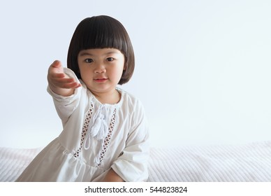 Happy asian child sitting on bed with white background
