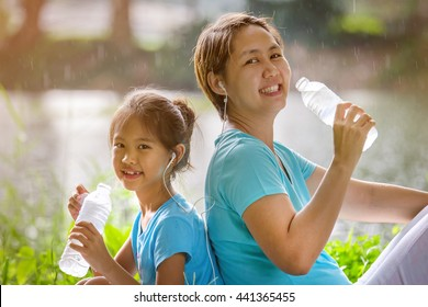 Happy Asian child and woman drinking fresh water together, Healthy family concept