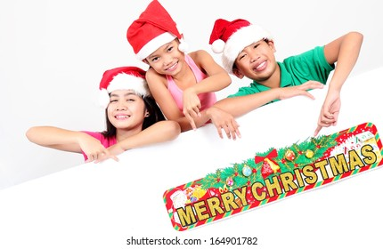 Happy asian children pointing to a christmas sign.