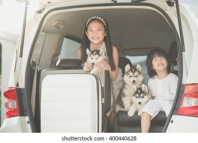 Happy asian children and siberian husky puppies sitting in the car
