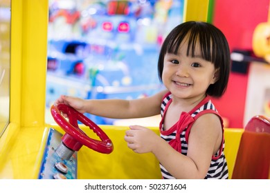 Happy Asian Chinese Little Girl Driving Toy Bus at indoor playground.