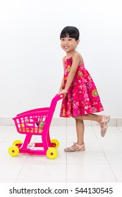 Happy Asian Chinese little girl pushing toy trolley in isolated white background.