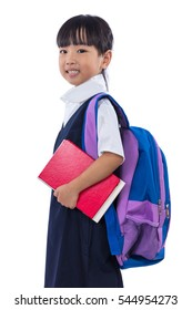 Happy Asian Chinese little primary school girl holding books with school bag in isolated white background.