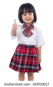 Happy Asian Chinese little student girl showing thumbs up in isolated white background.