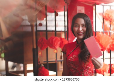 Happy Asian Chinese Woman in Cheongsam Traditional Red Dress Holding Red Envelope for Giving Ang Pao in Chinese Lunar New Year