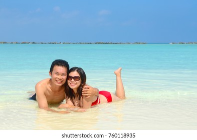 happy asian couple  in clean water at summer vacation in Maldives island