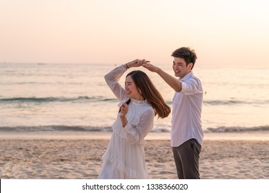 Happy Asian couple going honeymoon travel on tropical sand beach in summer