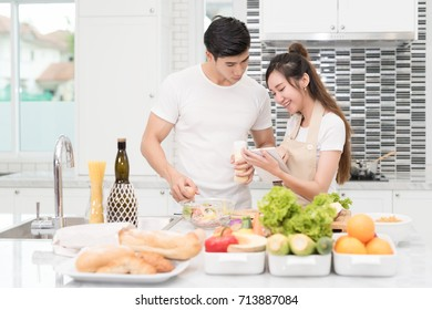 Happy asian couple in home kitchen filled with vegetables on the table, using electronic tablet device to see the recipe for their food