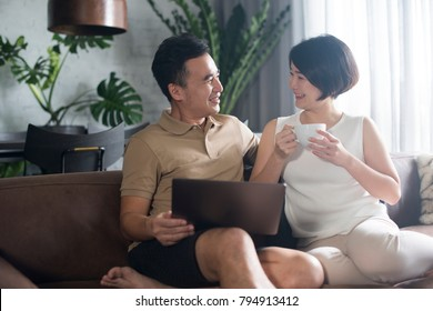Happy Asian couple looking at the computer and relaxing with a cup of coffee.