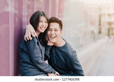 Happy Asian couple in love having fun and embracing outdoor in city