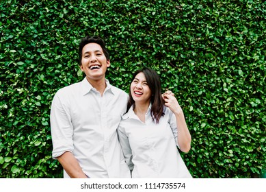 Happy Asian couple in love smiling and having fun while hugging outdoor