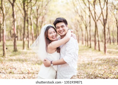 Happy Asian couple in love with tree arch at park