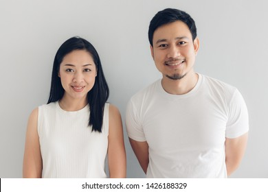 Happy Asian couple lover in white t-shirt and grey background.