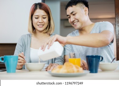 happy asian couple in pajamas sitting at table in kitchen at home in morning and having cereal breakfast together.husband pour milk into wife bowl