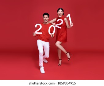 Happy asian couple in red casual  attire  showing number 2021 greeting happy new year with smiles on bright red background.