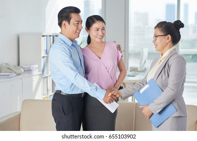 Happy Asian couple shaking hand of estate agent after meeting