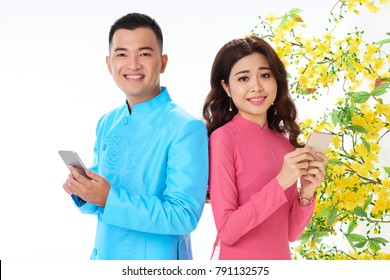 Happy Asian couple with smartphones, blooming apricot branches in the background