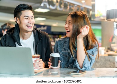 Happy asian couple take off face mask in a coffee shop surfing internet on laptop. Young man and woman in a restaurant looking at touch screen computer laugh smile together