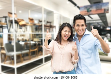 Happy Asian couple with thumb up in furniture showroom store