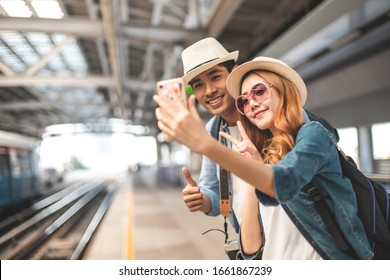 Happy Asian couple traveler holding a mobile phone in station and waiting for train in vacation time.Two Asian Tourists With Backpacks Train travel in Sightseeing City Thailand.