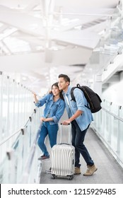 Happy Asian couple traveler with luggage at airport terminal