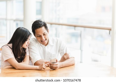 Happy Asian couple using smartphone indoor in modern building