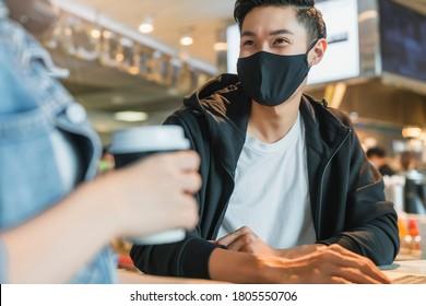 Happy asian Paar tragen Gesichtsmaske Virus Schutz in einem Café genießen gute Unterhaltung. Junge Männer und Frauen in einem Restaurant, das den Touchscreen-Computer anschaut, lachen zusammen