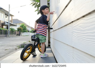 happy asian cute boy riding balance bike on street in front for home