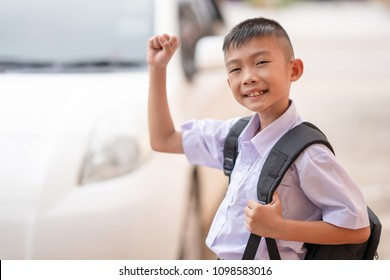Happy Asian cute child smiling and raising hand on uniform school for going to school in morning. Child boy holding bag or backpack and portrait photo happiness and funny. Blurred car for go to school
