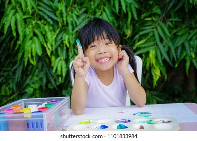 Happy Asian cute girl doing Fingerpaint, Soft Focus. Painting is play therapy for ADHD kids (Attention deficit hyperactivity disorder),can be used to address emotional problems.