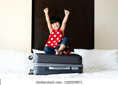 Happy Asian cute girl or kid is sitting on the baggage and ready to go to travel in aboard. Travel,tourism and journey concept.