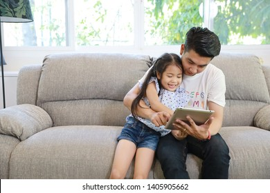happy asian dad teaching his daughter to use or play tablet on grey sofa in living room with laughing and smiling face (lifestyle with technology concept)