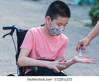 Happy asian disabled on wheelchair wearing Handmade mask and use alcohol to in the hands to protection flu Covid 19 or Coronavirus, Stay at home to prevent the spread of the virus disease 2020.