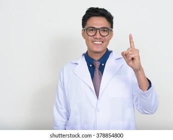Happy Asian doctor pointing finger up
