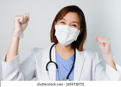 Der glückliche asiatische Arzt trägt die medizinische Maske, um die Infektion vor Keimen, Bakterien, Covid19, Corona, Saren, Grippevirus auf weißem Hintergrund mit dem glücklichen Gesicht zu schützen und zu bekämpfen.