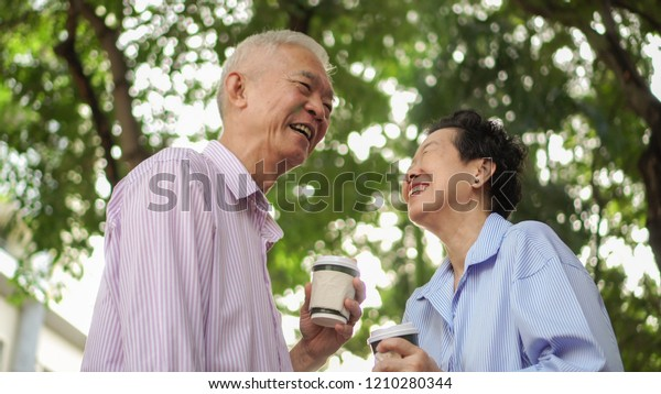 Happy Asian elderly couple morning walk in green city drinking coffee and talking