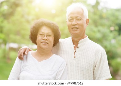 Happy Asian elderly couple smiling at outdoor park on a sunny day.