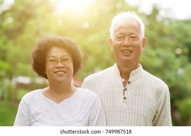 Happy Asian elderly couple smiling at outdoor park.