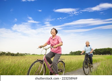 Happy Asian elderly seniors couple biking in farm with blue sky background