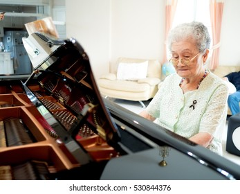 Happy Asian elderly woman pianist playing piano at home. Retirement woman relaxed by learning to play piano.