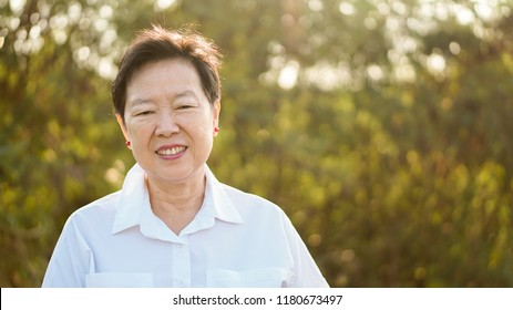 Happy Asian elderly woman smiling in morning sun with green nature background