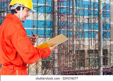 Happy Asian engineers writing the note pad on construction site workers, industrial construction concept