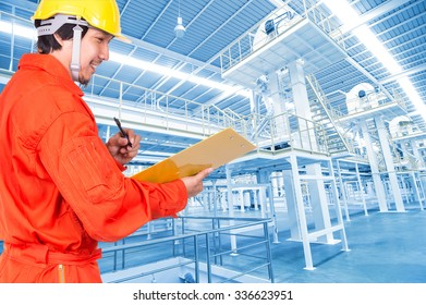 Happy Asian engineers writing the note pad on Factory equipment inside Industrial conveyor line transporting package, industrial concept