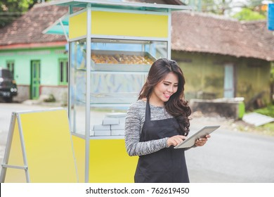 happy asian entrepreneur with her newly open small business food stall. promoting online using tablet pc